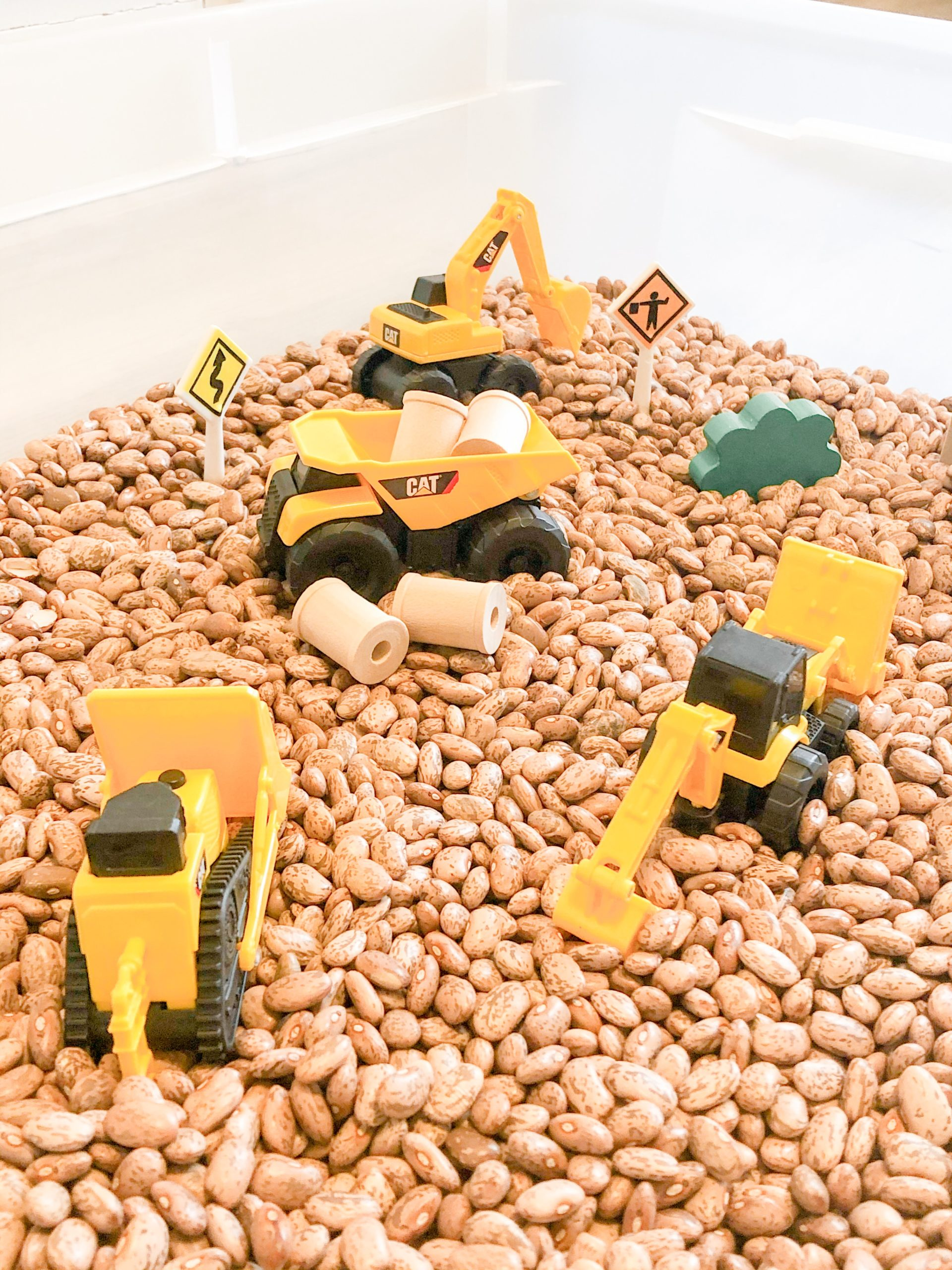 Sensory bin with construction trucks and vehicles. Sensory activity for toddlers.