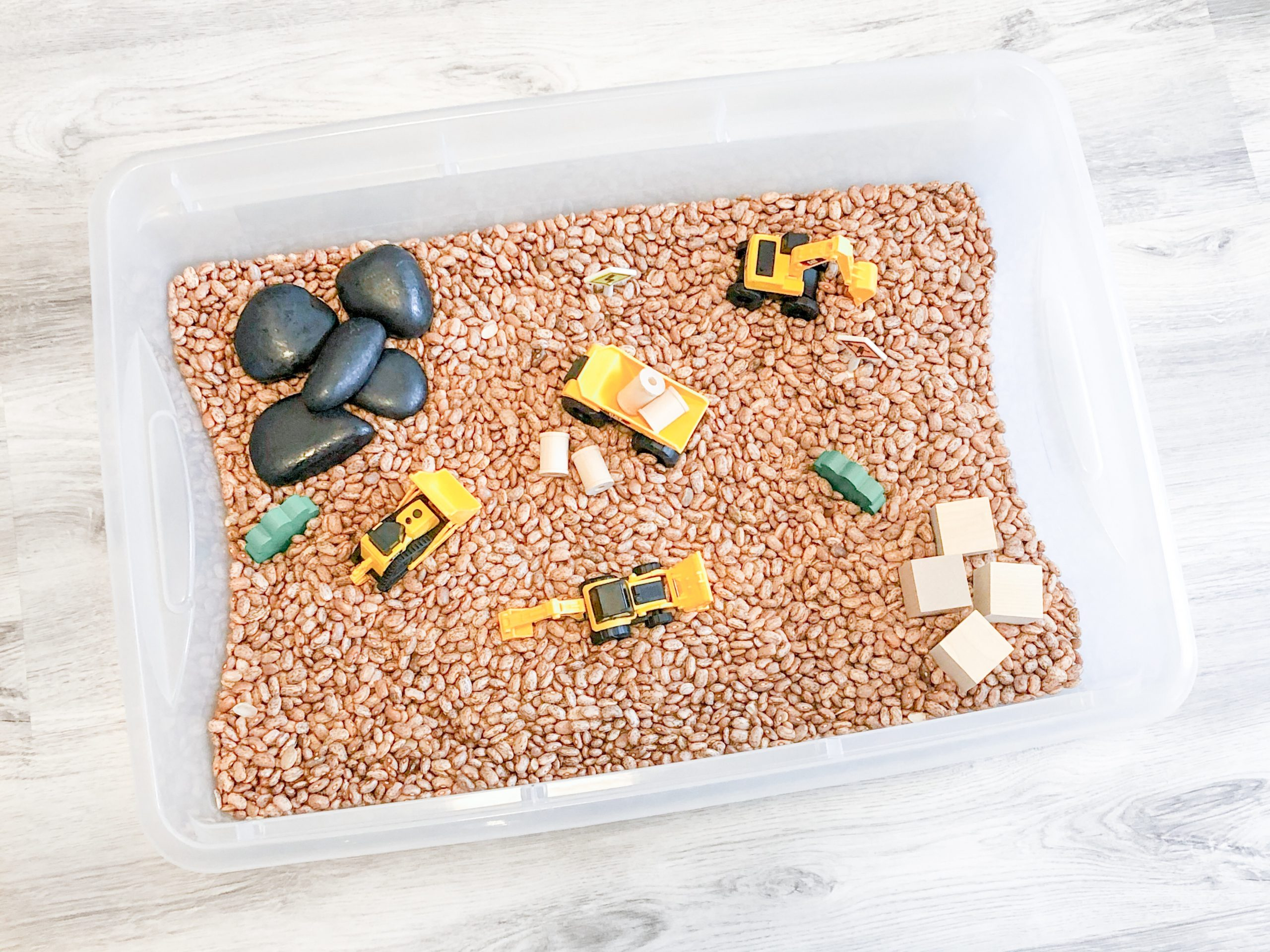 Construction sensory bin with pinto beans. An easy DIY sensory bin that is fun for a variety of ages.